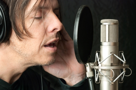 Close-up of a serious man recording vocals in a sound studio.