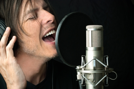 Close-up of a man singing into a condenser microphone.