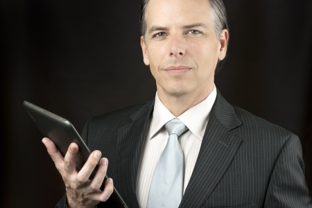 Close-up of a confident businessman holding  tablet. photo