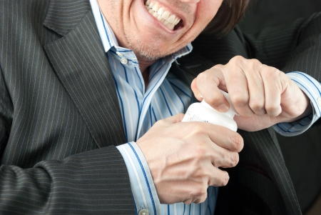 Close-up of a frustrated businessman trying to open a pill bottle. Stock Photo - 14900658