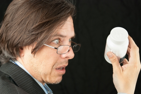 Close-up of a casual businessman looking over glasses trying to read a pill bottle label. Stock Photo - 14900650
