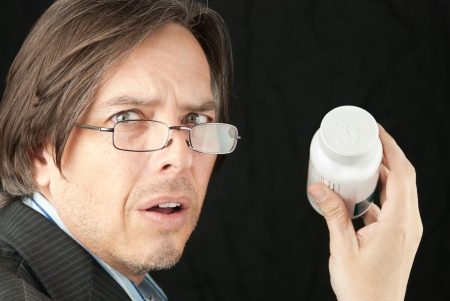 Close-up of a casual businessman wearing glasses frustrated trying to read a pill bottle label. Stock Photo - 14900646