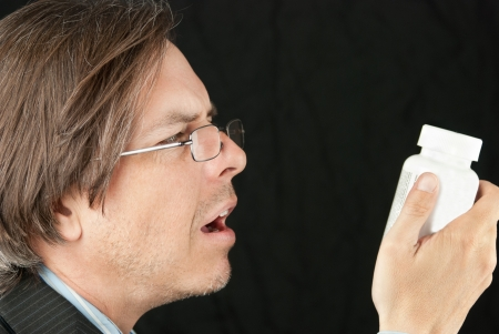 Close-up of a casual businessman wearing glasses trying to read a pill bottle label. Stock Photo - 14900648