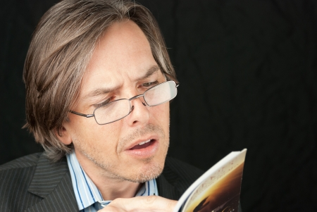 Close-up of a casual businessman wearing glasses reading a book. Stock Photo - 14900643