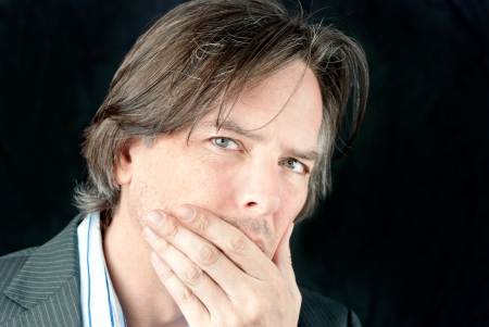 Close-up of a ill businessman covering his mouth.