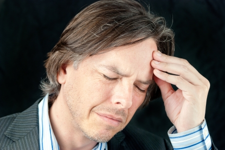 lifestyle disease: Close-up of a businessman rubbing his forehead.