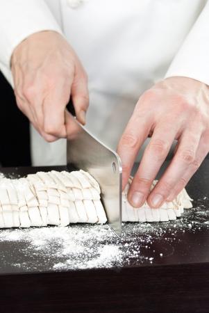 culinary skills: Close-up of a Chef cutting fresh pasta. Stock Photo