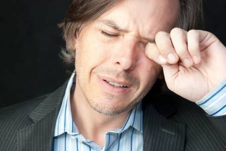 Close-up of a stressed businessman rubbing his eyes. Stock Photo - 14900675