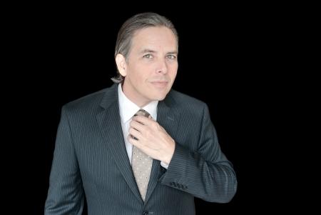 waistup: Close-up of a businessman adjusting his tie, waist-up  Stock Photo