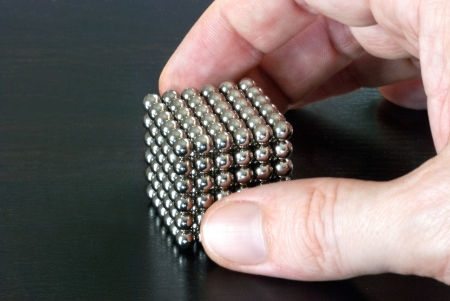chrome man: Close-up of a hand pickinf up a cube composed of magnetic balls