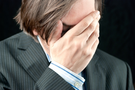 Close-up of a businessman holding his head and covering his face with his hand  photo