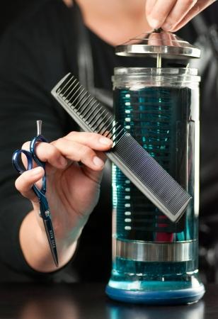 desinfectante: Primer plano de un estilista de la colocación de un peine en un recipiente de vidrio transparente lleno de desinfectante de panales.