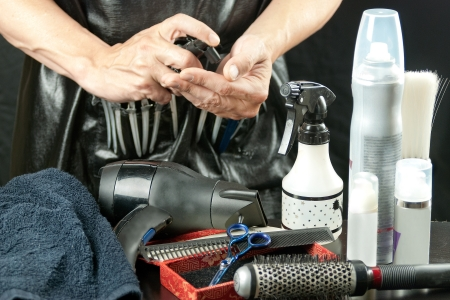 barbershop: Close-up of a stylist surrounded by his tools spraying mousse into his hand.
