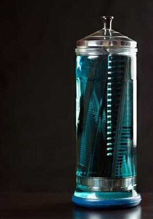 d�sinfectant: Gros plan d'un r�cipient en verre clair de d�sinfectant compl�te de peignes.