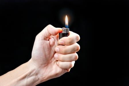 encendedores: Primer plano de la mano de un hombre sosteniendo un encendedor iluminado. Foto de archivo