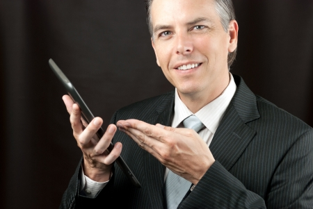 Close-up of a businessman showing his tablet. Stock Photo