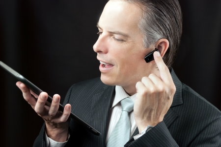 earpiece: Close-up of a businessman using a tablet adjusting his earpiece headset.
