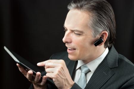 earpiece: Close-up of a businessman wearing an earpiece headset using a tablet.