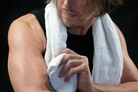 Close-up of a man wiping of his arm after his workout. photo
