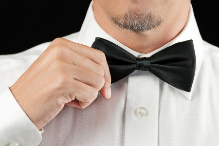 Close-up of a man in a tux straightening his bowtie, one hand, no jacket  Stock Photo