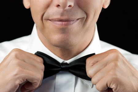 bowtie: Close-up of a man in a tux straightening his bowtie, two hands, no jacket  Stock Photo