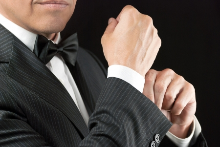 Close-up of a man in a tux fixing his cufflink  Stock Photo