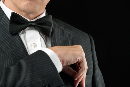 hands in pockets: Close-up of a man in a tux tucking in his pocket square
