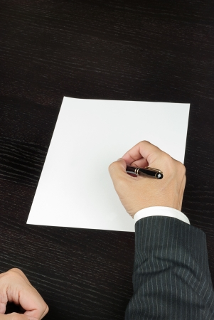 Close-up of a businessman writing, shot from above  photo