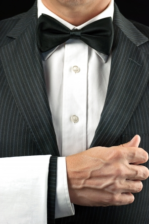 Close-up torso shot of a fine dining waiter in a bowtie and tux with a white pressed napkin over his arm