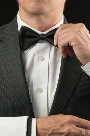 Close-up torso shot of a fine dining waiter in a bowtie and tux adjusting his bowtie with a white pressed napkin over his arm