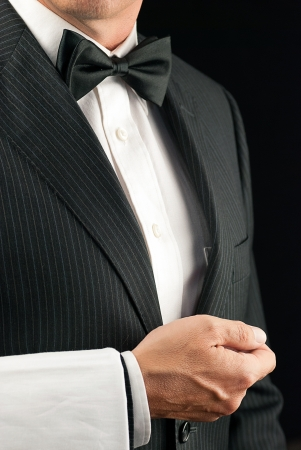 Close-up torso shot of a fine dining waiter in a bowtie and tux with a white pressed napkin over his arm  Side View