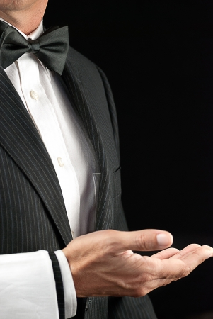 Close-up torso shot of a fine dining waiter in a bowtie and tux with a white pressed napkin over his arm,with his hand open and palm facin gup  Side View  photo