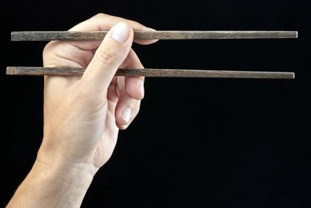 Close-up of a hand holding chopsticks  photo