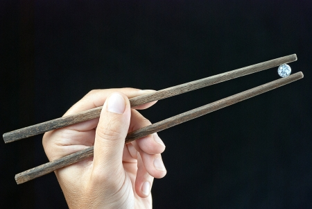 Close-up of a hand holding a gem using chopsticks