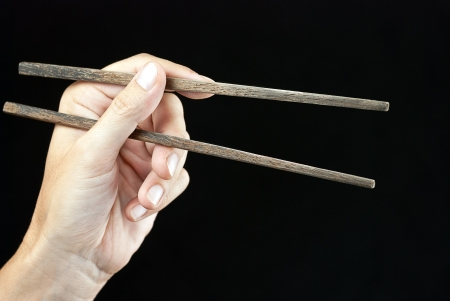 Close-up of a hand holding open chopsticks  photo