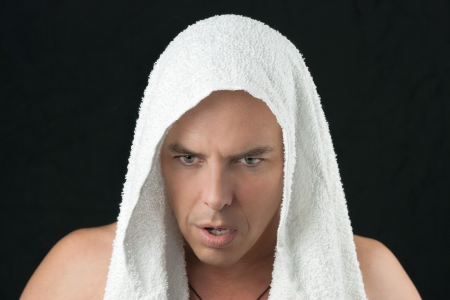 Close-up of a intense man thinking, workout towel over head, looking down  photo