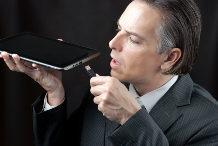 plugging: Close-up of a businessman plugging a usb cable into his tablet Stock Photo