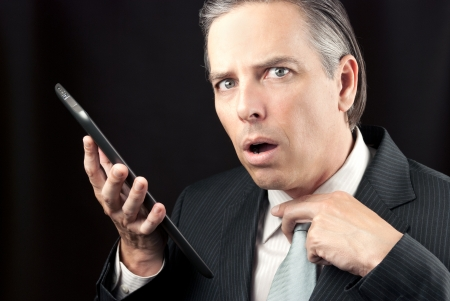 Close-up of a businessman using his tablet and looking to camera with concern photo