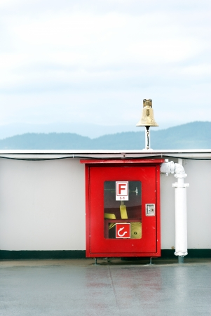 alarmed: Close-up of a locked, alarmed fore hose box on a bridge  Mountains in the horizon