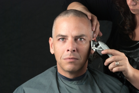 shaved: Close-up of a mourning man getting his head shaved. Looking to camera,