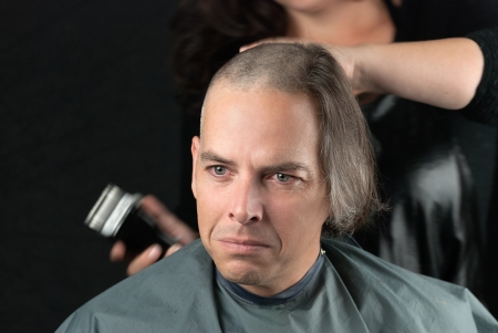 Close-up of a mourning man getting his long hair is shaved off for a cancer fundraiser.
