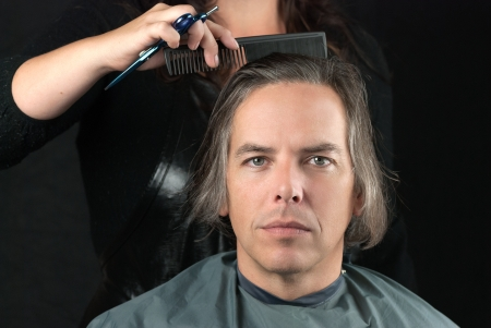 combed: Close-up of a serious man looking to camera while his hair is combed in preparation for having it cut off for a cancer fundraiser.