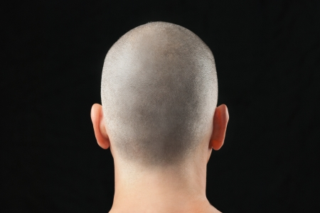 Close-up of a buddhist man with a newly shaved head, shirtless and shot from behind
