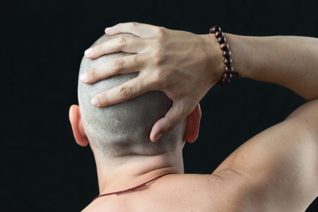 shaved: Close-up of a buddhist man wearing a mala feeling his newly shaved head, shirtless and shot from behind  Stock Photo