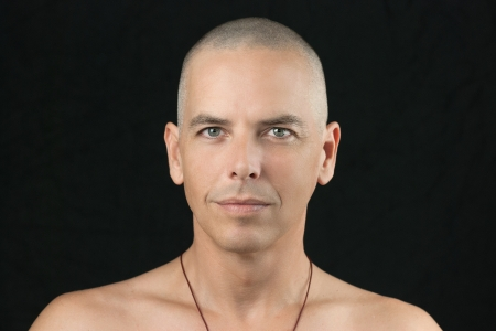 Close-up of a buddhist man looking to camera, shaved head and shirtless  版權商用圖片