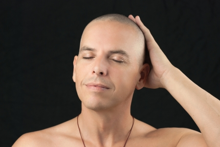 Close-up of a buddhist man feeling his newly shaved head, shirtless  Stock Photo