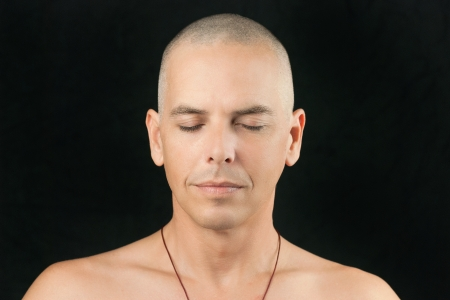 shaved: Close-up of a man meditating, shaved head and shirtless  Stock Photo