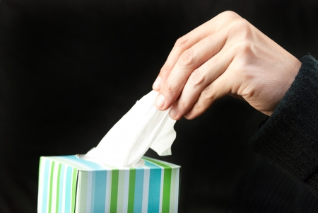 Close-up of a mans hand pulling a tissue out of the box. photo