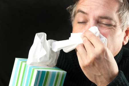 Close-up of a man blowing his nose while holding a tissue box. Stock Photo