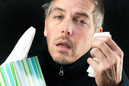Close-up of a man exhausted by allergies/cold/flu holding a tissue and the box. Stock Photo - 25226669